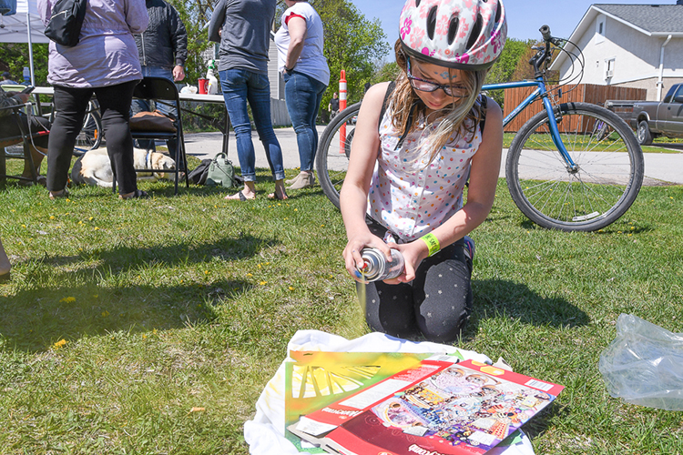 Anika Rumpli has fun decorating a t-shirt during the Bike Week opening Saturday at the Greasy Chain shop.    Mickey Dumont/Citizen photo