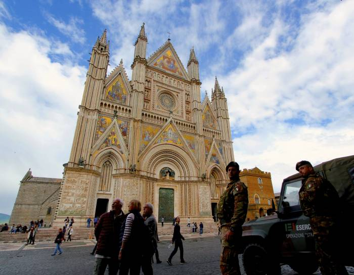 Italian soldiers guard the gold-gilded facade of Orvieto's cathedral